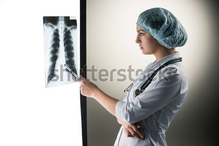 Image of attractive woman doctor looking at x-ray results Stock photo © master1305