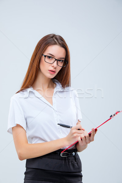 The young business woman with pen and tablet for notes on gray background Stock photo © master1305