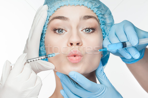 Attractive woman at plastic surgery with syringe in her face Stock photo © master1305