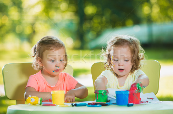 Two-year old girls painting with poster paintings together against green lawn Stock photo © master1305