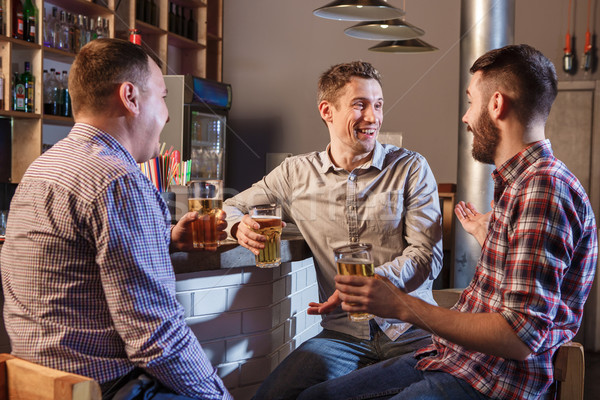 Happy friends drinking beer at counter in pub Stock photo © master1305