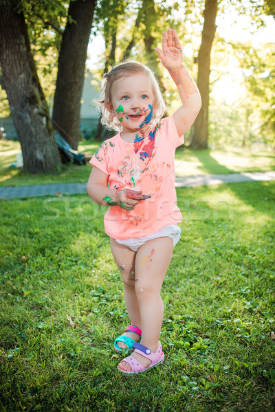 Two-year old girl stained in colors against green lawn Stock photo © master1305