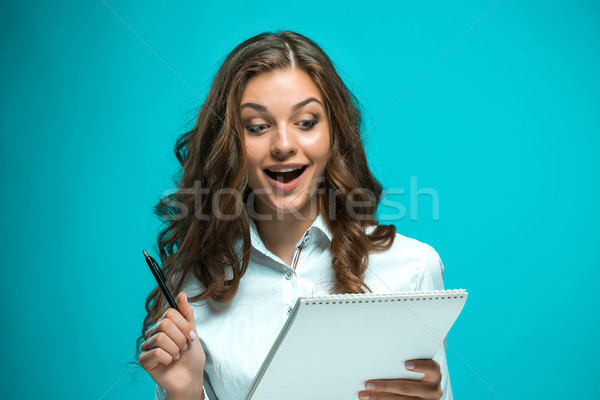Surprised young business woman with pen and tablet for notes on blue background Stock photo © master1305