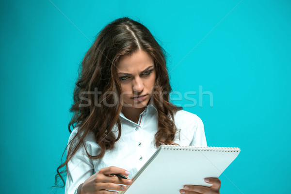 The displeased young business woman with pen and tablet for notes on blue background Stock photo © master1305