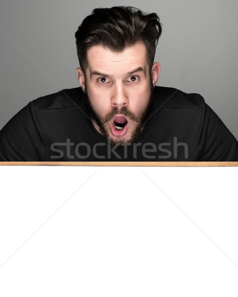The surprised man and empty blank over gray background Stock photo © master1305