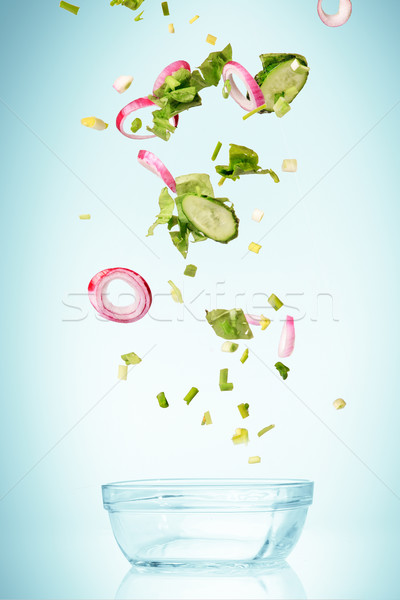 Stock photo: The vegetables for salad falling on blue