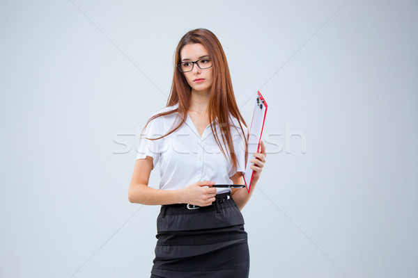 Stock photo: The young business woman with pen and tablet for notes on gray background