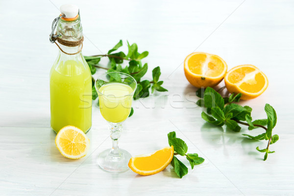 Stock photo: Home orange liquor in a glass and fresh oranges on the white wooden background