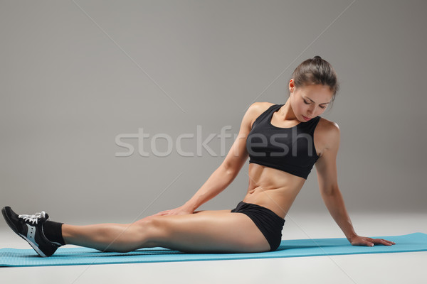 Muscular young woman athlete stretching on gray  Stock photo © master1305