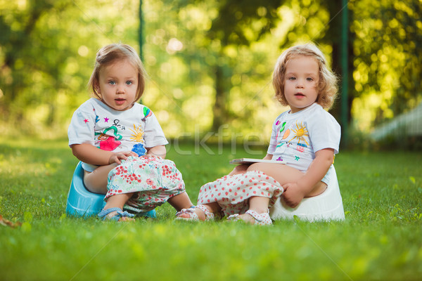 The two little baby girls sitting on pots Stock photo © master1305