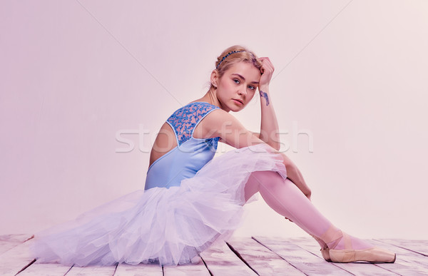 Stock photo: Tired ballet dancer sitting on the wooden floor