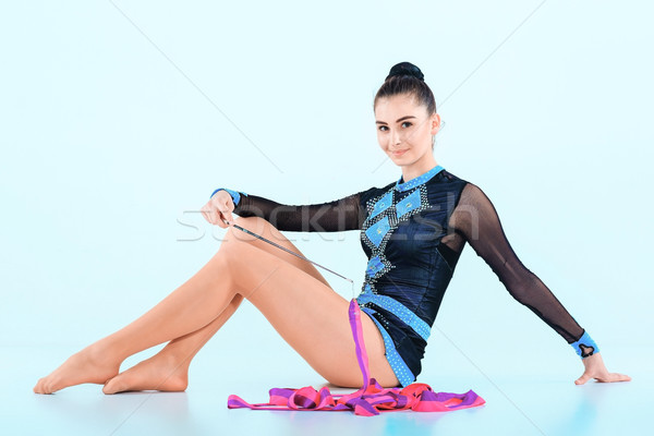 The girl sitting with colored ribbon on a blue background Stock photo © master1305
