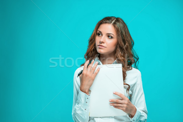 Stock photo: The thoughtful young business woman with pen and tablet for notes on blue background