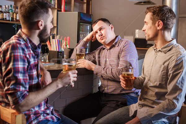 The  friends drinking beer at counter in pub Stock photo © master1305