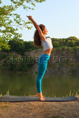 Young woman is practicing yoga near river Stock photo © master1305