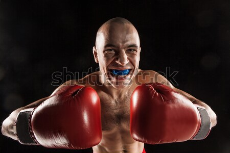 The young man kickboxing on black  with screaming face Stock photo © master1305