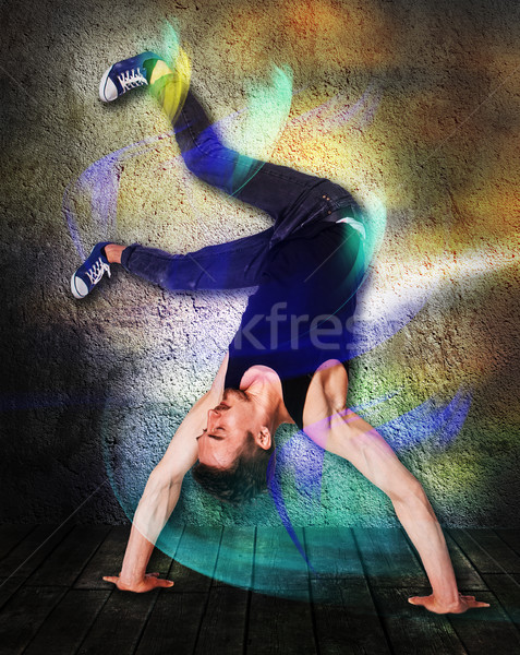 Break dancer doing handstand against colorful wall background Stock photo © master1305