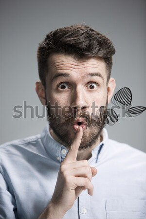 Man is looking wary. Over gray background Stock photo © master1305