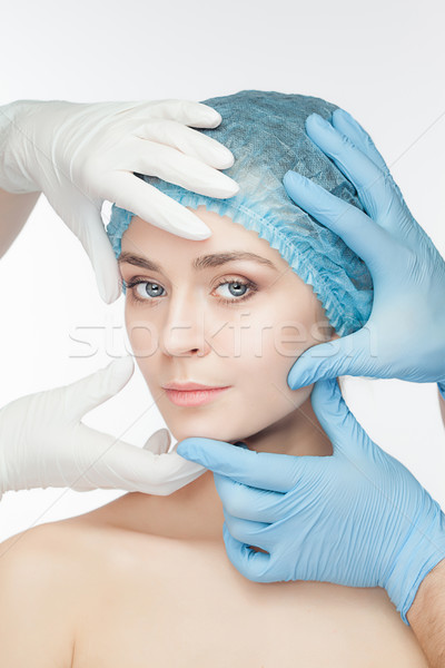 Plastic surgery concept. Doctor hands in gloves touching the beautiful woman face on white Stock photo © master1305
