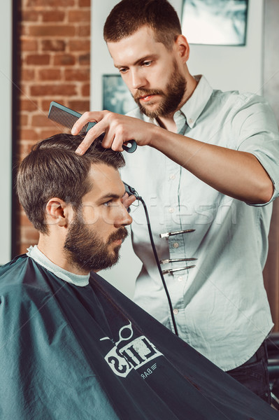 Young handsome barber making haircut of attractive man in barbershop Stock photo © master1305