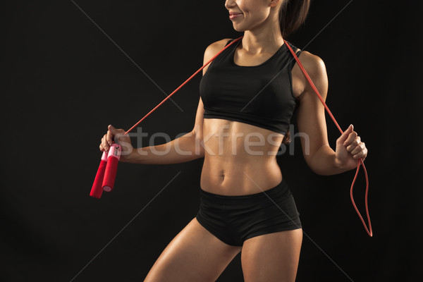 Muscular young woman athlete with a skipping rope on black  Stock photo © master1305