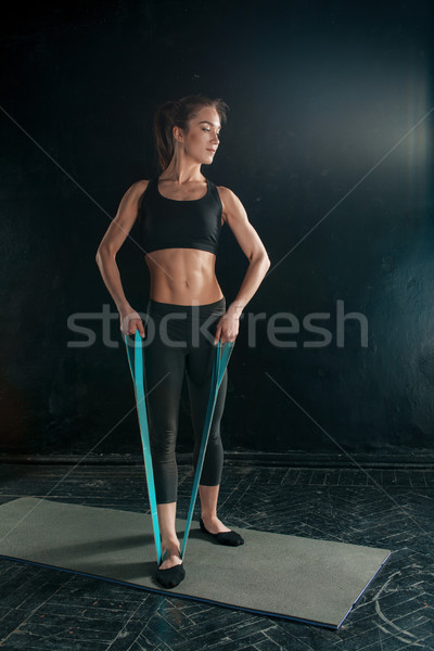 Stock photo: Beautiful slim brunette doing some stretching exercises in a gym