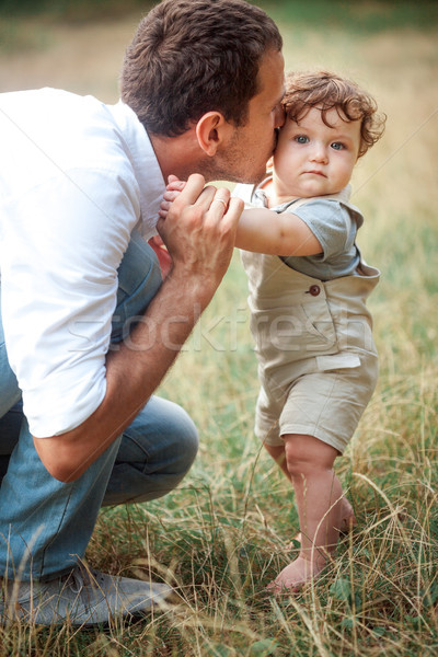 Young beautiful father and little toddler son against green grass Stock photo © master1305