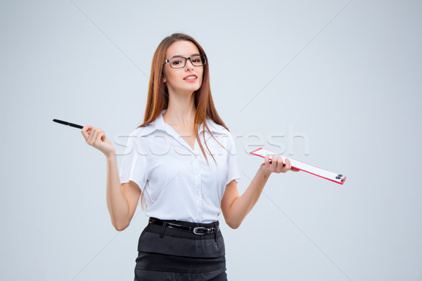 Stock photo: The smiling young business woman with pen and tablet for notes on gray background