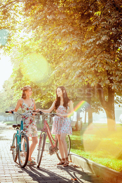 The two young girls with bicycles in park Stock photo © master1305