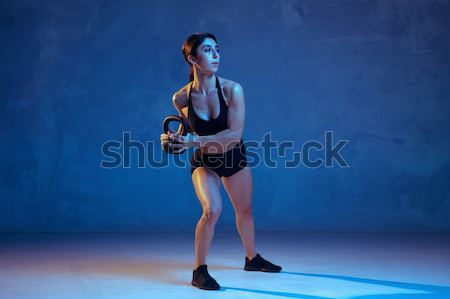 Muscular young woman athlete with a skipping rope on blue Stock photo © master1305