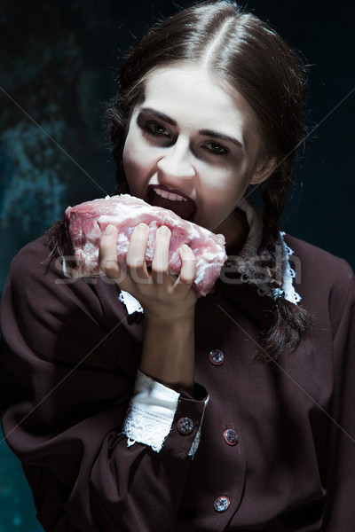 Bloody Halloween theme: crazy girl with raw meat stock photo
