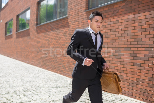Stock photo: Chinese young businessman running in a city street