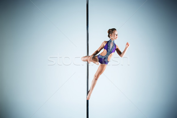 The strong and graceful young girl performing acrobatic exercises on pylon Stock photo © master1305