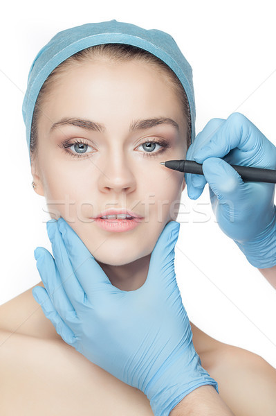 Beautiful young woman with perforation lines on her face before plastic surgery operation. Stock photo © master1305
