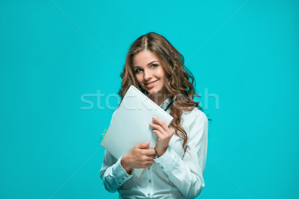 The smiling young business woman with pen and tablet for notes on blue background Stock photo © master1305
