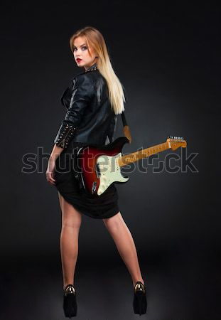 Stock photo: Beautiful young blonde dressed in black leather with electric guitar