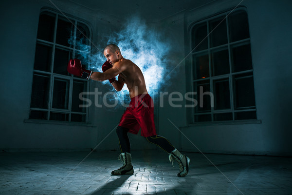 The young man kickboxing in blue smoke Stock photo © master1305