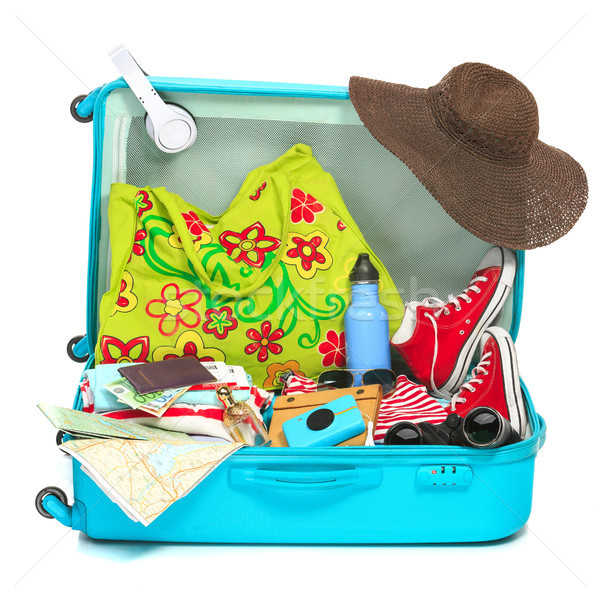 The open blue suitcase, sneakers, clothing, hat, and retro camera on white background. Stock photo © master1305