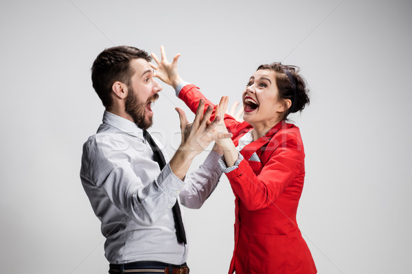 The business man and woman laughing on a gray background Stock photo © master1305