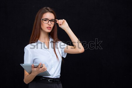 Stock photo: The young business woman with tablet on black background
