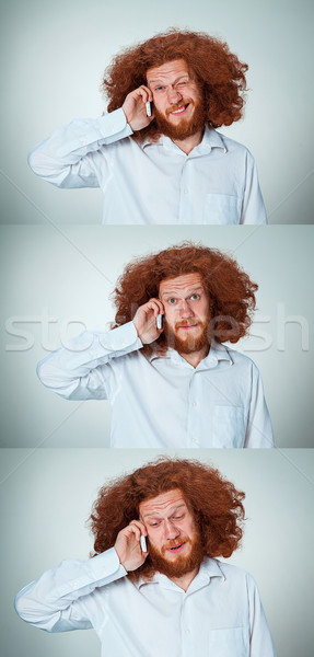 Portrait of puzzled man talking on the phone  a gray background Stock photo © master1305