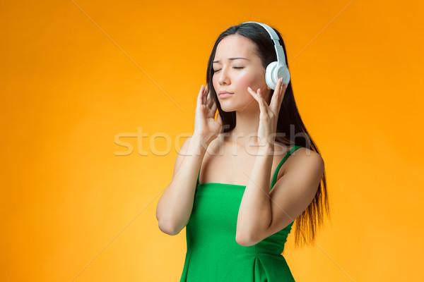 Cute alegre nina naranja escuchar música auriculares Foto stock © master1305