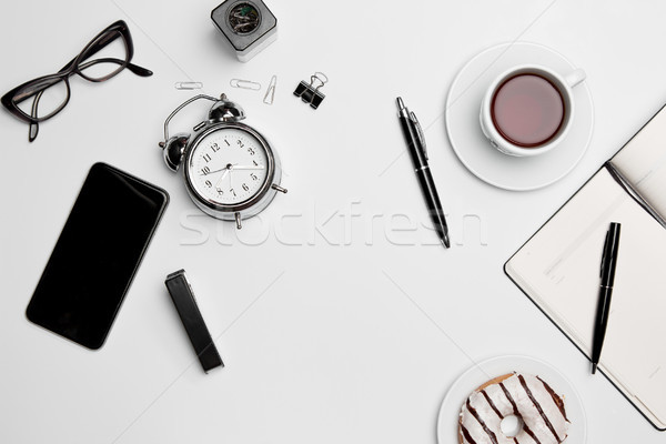 Office desk table with cup, supplies, phone on white background Stock photo © master1305