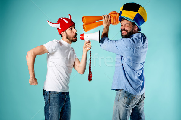 The two football fans with mouthpiece over blue Stock photo © master1305