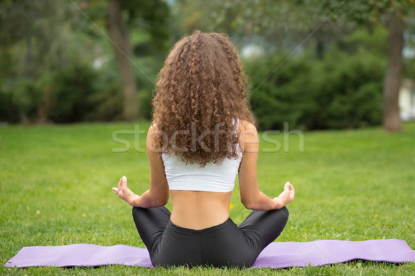Pretty woman sitting back doing yoga meditation Stock photo © master1305