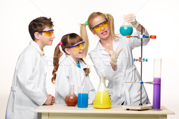 Teens and teacher of chemistry at  lesson making experiments Stock photo © master1305