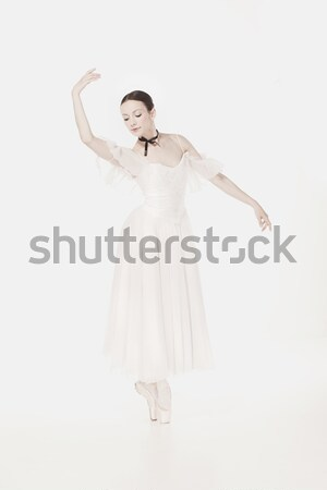 Stock photo: Ballerina in white dress posing on pointe shoes, studio background.