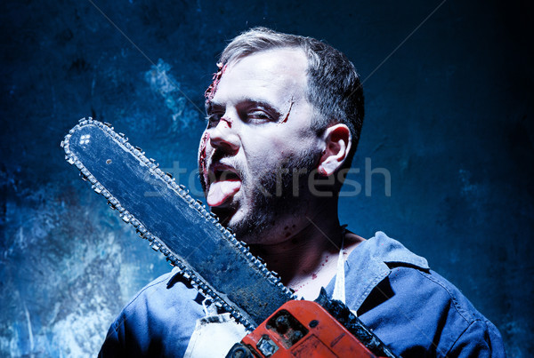 Bloody Halloween theme: crazy killer as butcher with electric saw Stock photo © master1305