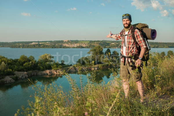 Young caucasian man with backpack standing on the top of hill Stock photo © master1305