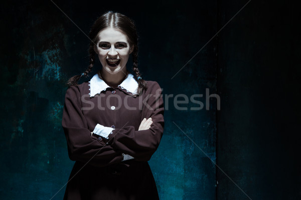 Portrait of a young smiling girl in school uniform as killer woman Stock photo © master1305